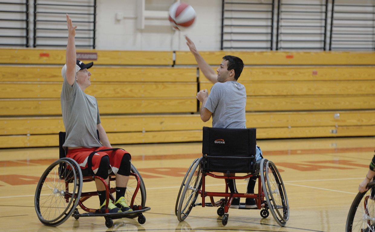 High school student Josh Montgomery passes the ball over the top of classmate David Cropper during a game of wheelchair basketball Friday morning at Steamboat Springs High School. Steamboat Adaptive Recreational Sports has expanded adaptive PE programs at Steamboat schools this year, including through games of wheelchair basketball.