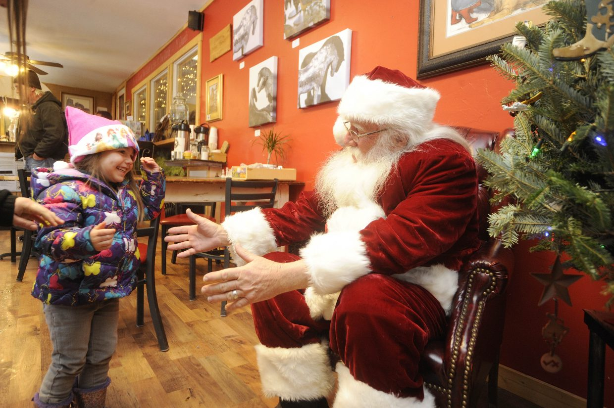 Elaina Raleigh, 3, visits Santa on Saturday during the Holiday Stroll in Hayden.