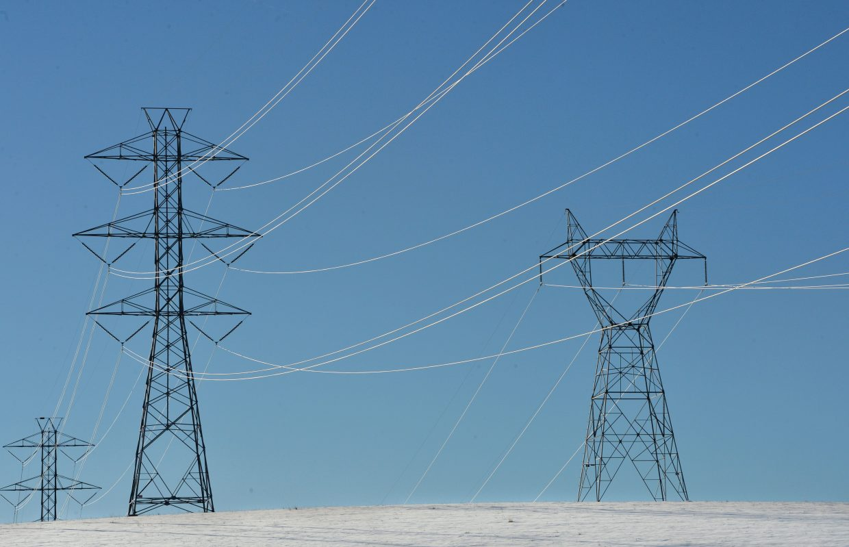 Power lines crisscross a blue mountain sky southwest of Steamboat Springs on Monday afternoon.