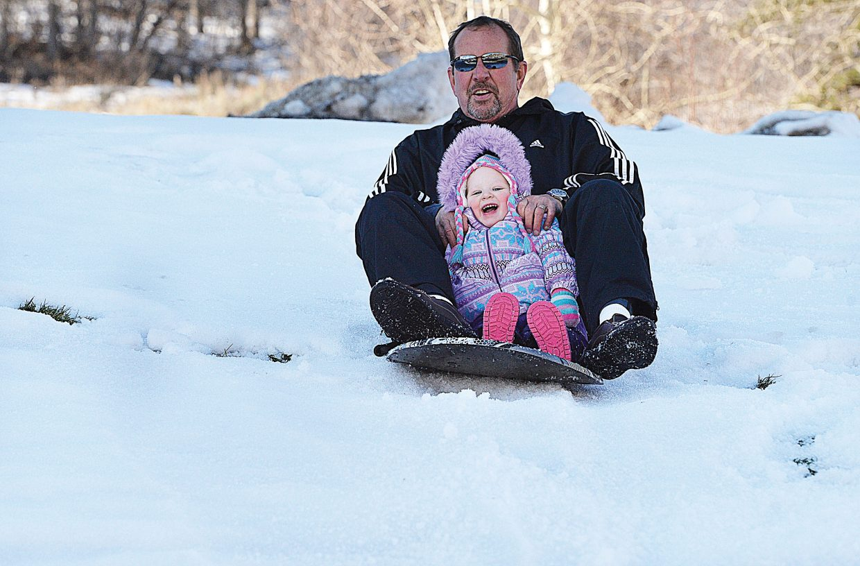 Joe Quinn rides down a hill with his granddaughter Harper Toyer on Monday afternoon at Colorado Mountain College.