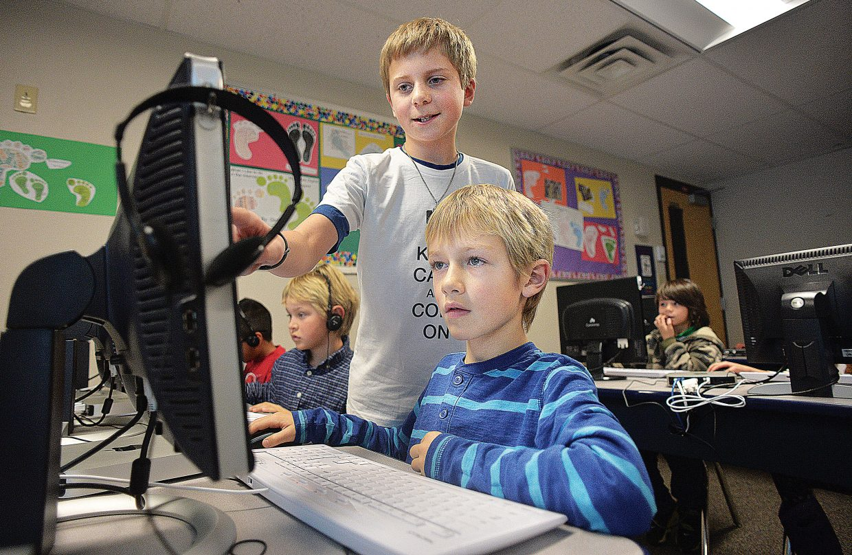 Fifth-grader Ben Schott helps second-grader Shamus Davenport with a computer during an Hour of Code at Strawberry Park Elementary School. The program has older students helping younger ones with the basics of computer programming.