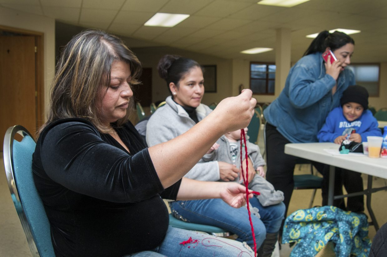Maria Landa weaves a red belt for a child to wear as part of traditional costume during Fiesta de la Guadalupe at St. Michael's Catholic Church. Landa gathers with other women, including Maria Elena Rizo, middle, Brenda Tarango and her son, Otoniel Tarango, right, every Wednesday during catechism classes at the church to offer help and support to the classes and the kids.