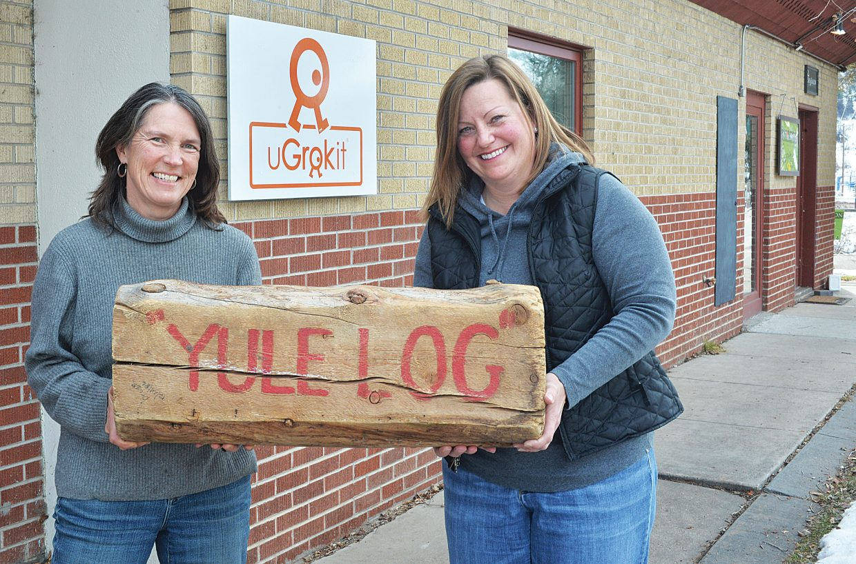 Laura Sankey, left, and Jennifer Meeks hold up the Yule Log after finding it near the Steamboat Springs Chamber Resort Association's building off of U.S. Highway 40. Sankey said she was thrilled to find the log, but sad that the hunt for 2014 was over for the year.