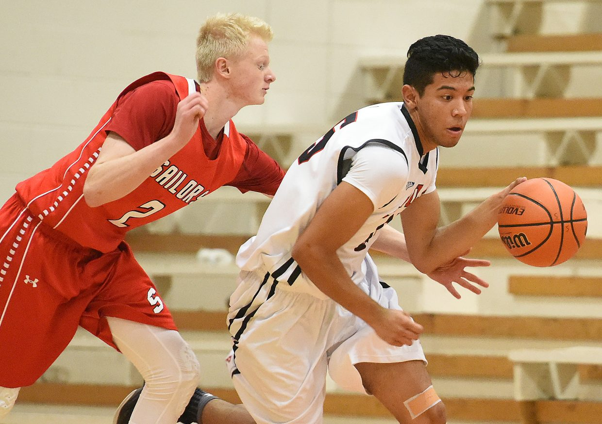 Ethan Riniker tries to reach around Eagle Valley's Jesse Loera to poke the ball away Saturday. The Sailors went on to win the game, 57-46.