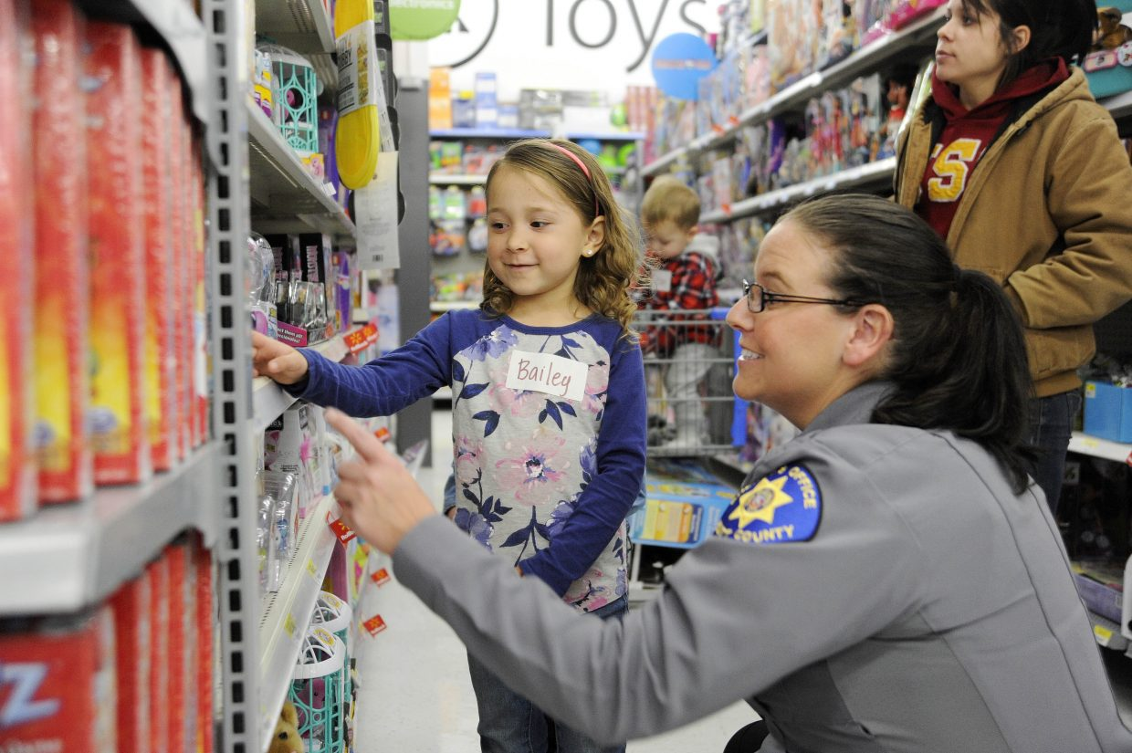 Five-year-old Bailey Fernandez shops with Routt County Sheriff's Office Deputy Lisa Wilson on Sunday at Walmart during a holiday Shop With a Cop event.