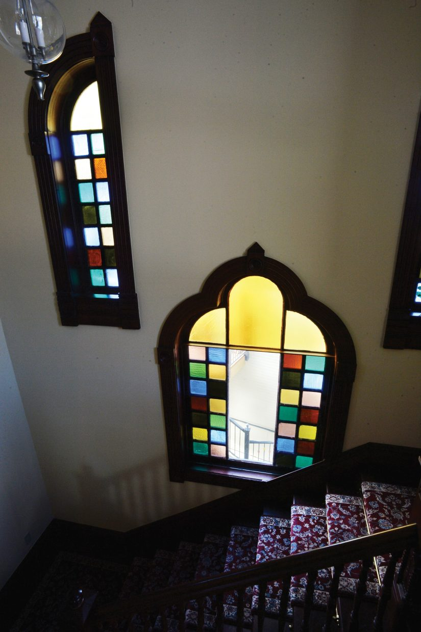 Afternoon light pours through the stain glass windows of the Victorian, spotlighting a pair of grand staircases that take visitors to all the levels of the home.