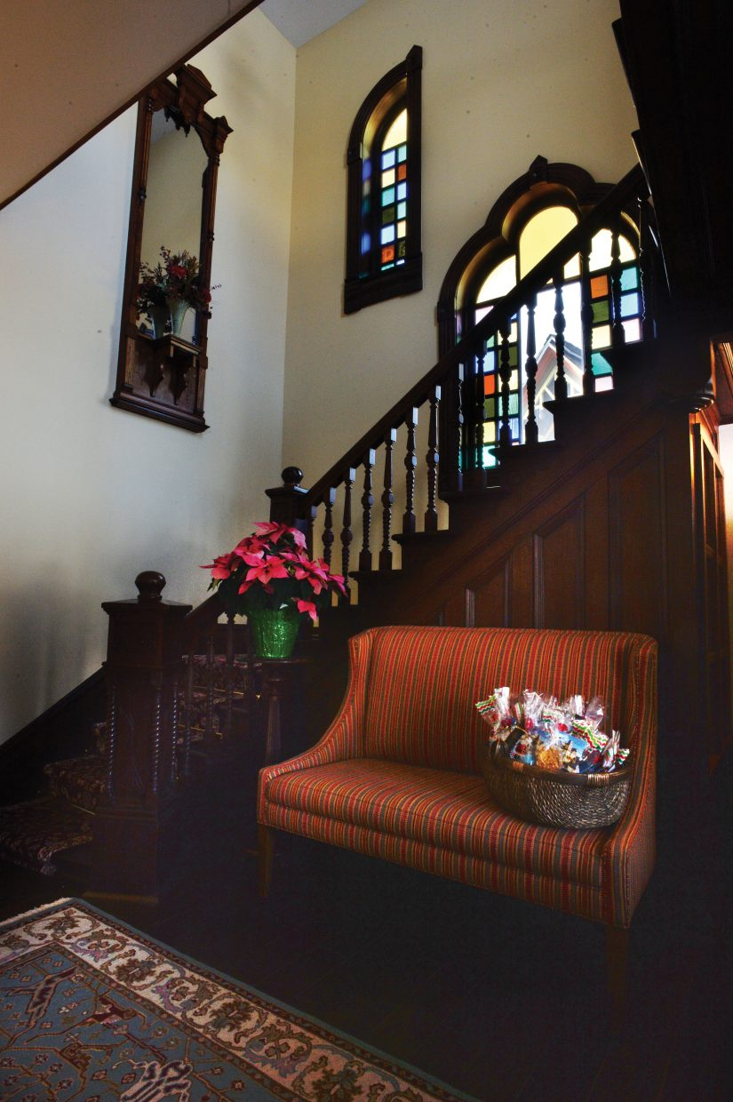 The entryway of the Victorian features a grand staircase and lots of stained glass.