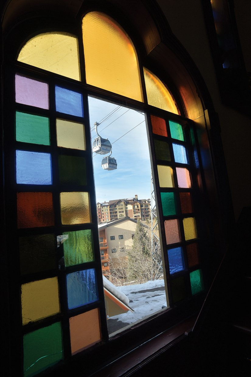 Gondola cars from Steamboat Ski Area pass in front of one of the stain glass windows at the Victorian bed and breakfast at the base of the mountain.