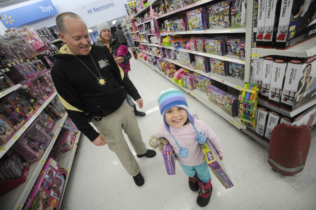 Sarah Chamberlain shops with Routt County Sheriff's Office Cpl. Ryan Adrian during Shop With a Cop on Saturday at Walmart.