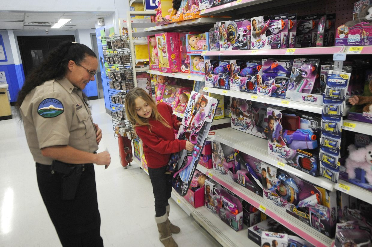 Gracy Tuttle shops with Routt County Sheriff's Office Lt. Michelle Richardson during Shop With a Cop on Saturday at Walmart.