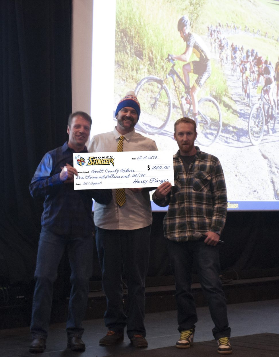 Big Agnes and Honey Stinger employees and Routt County Riders board members Rob Peterson and Nate Bird present a check for $1,000 to Alan Perkins, Routt County Riders board president. The money was raised through the Steamboat Stinger race.