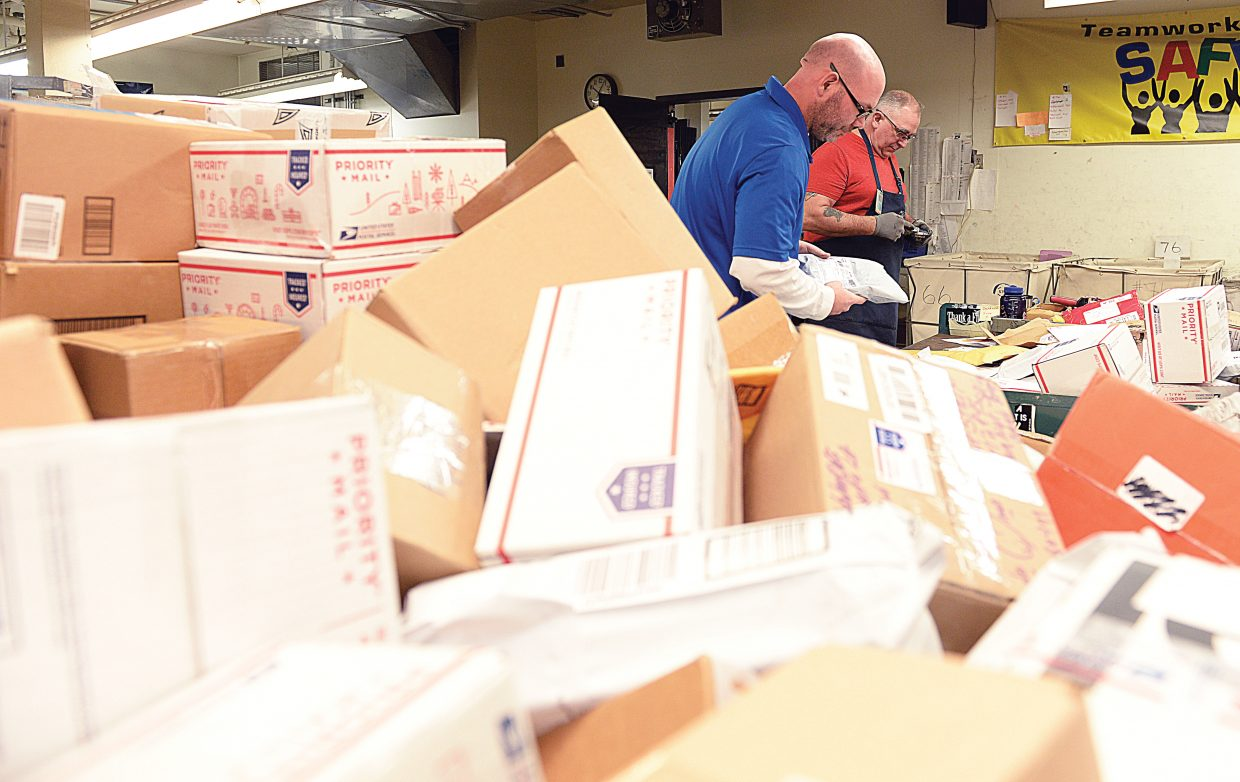 Post office employees, including Josh Styron, front, and Dave Puckett, were busy little elves Friday morning sorting through packages and making sure they got delivered in time to be placed under the Christmas tree on Sunday.