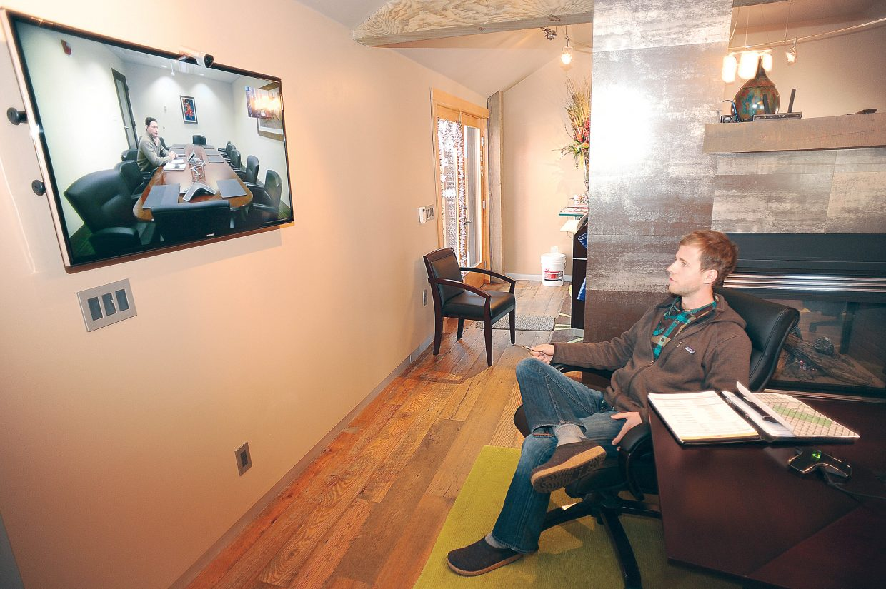Eric Schneider, sitting in Green Courte Partners' Steamboat Springs office, talks with Eric Dowling in the firm's Chicago area office over a video call. Advances in technology have made it easier for more people to work and live where they want.