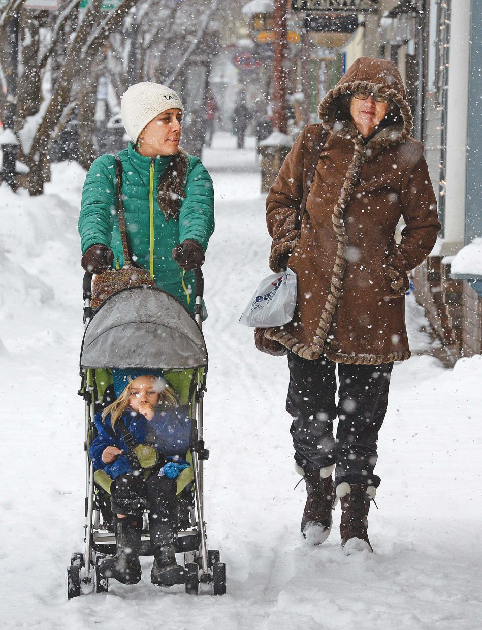 Kelly Schaffer pushes her son Diego through the snow in downtown Steamboat Springs Monday while walking with her mom Linda during a holiday shopping trip.
