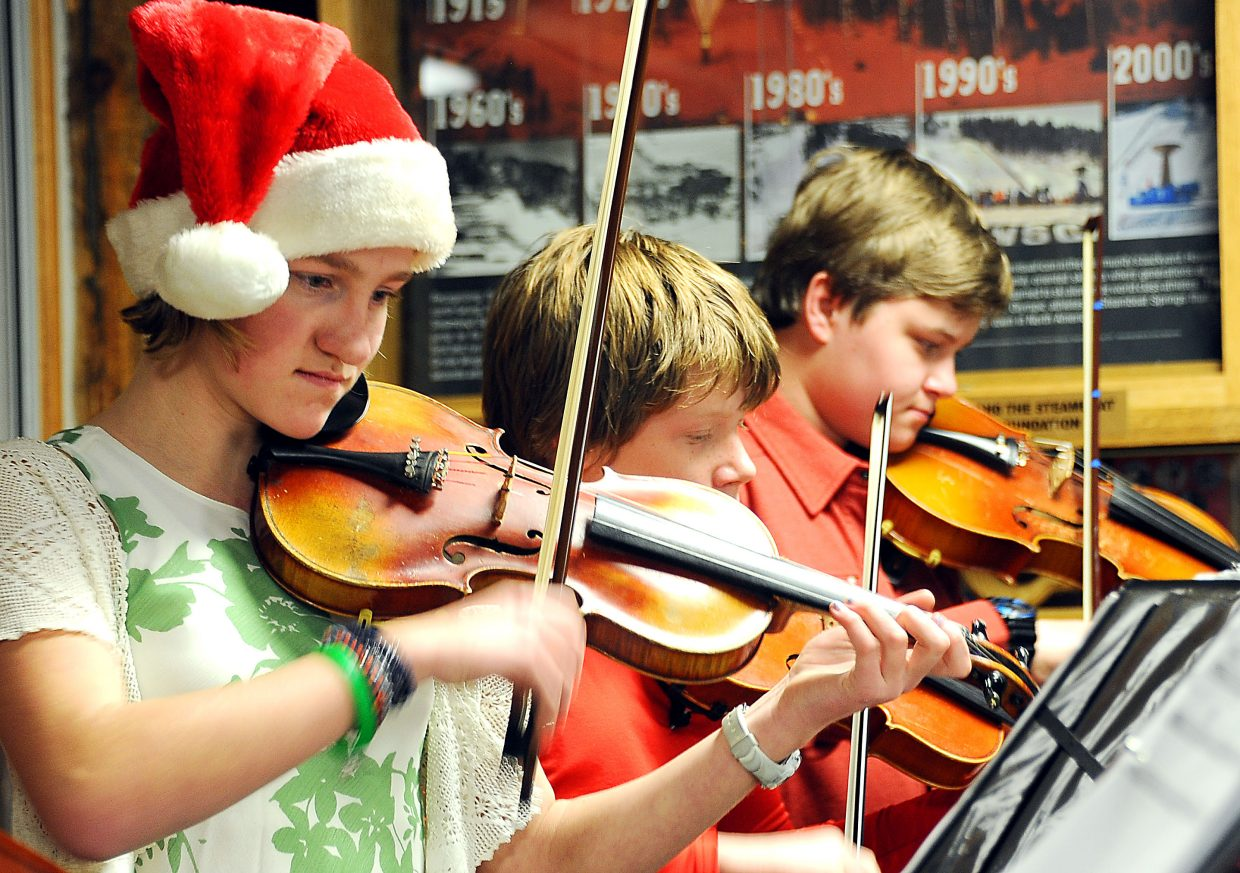 Macayla Scheidt focuses on the music while playing violin at the Holiday Wishes party at Howelsen Hill in Steamboat Springs. She joined up with fellow Emerald Mountain School eighth-graders Hayden Entress, Colton Oleski, Silas Boatwright and Rhys Morgan to play carols during the event.