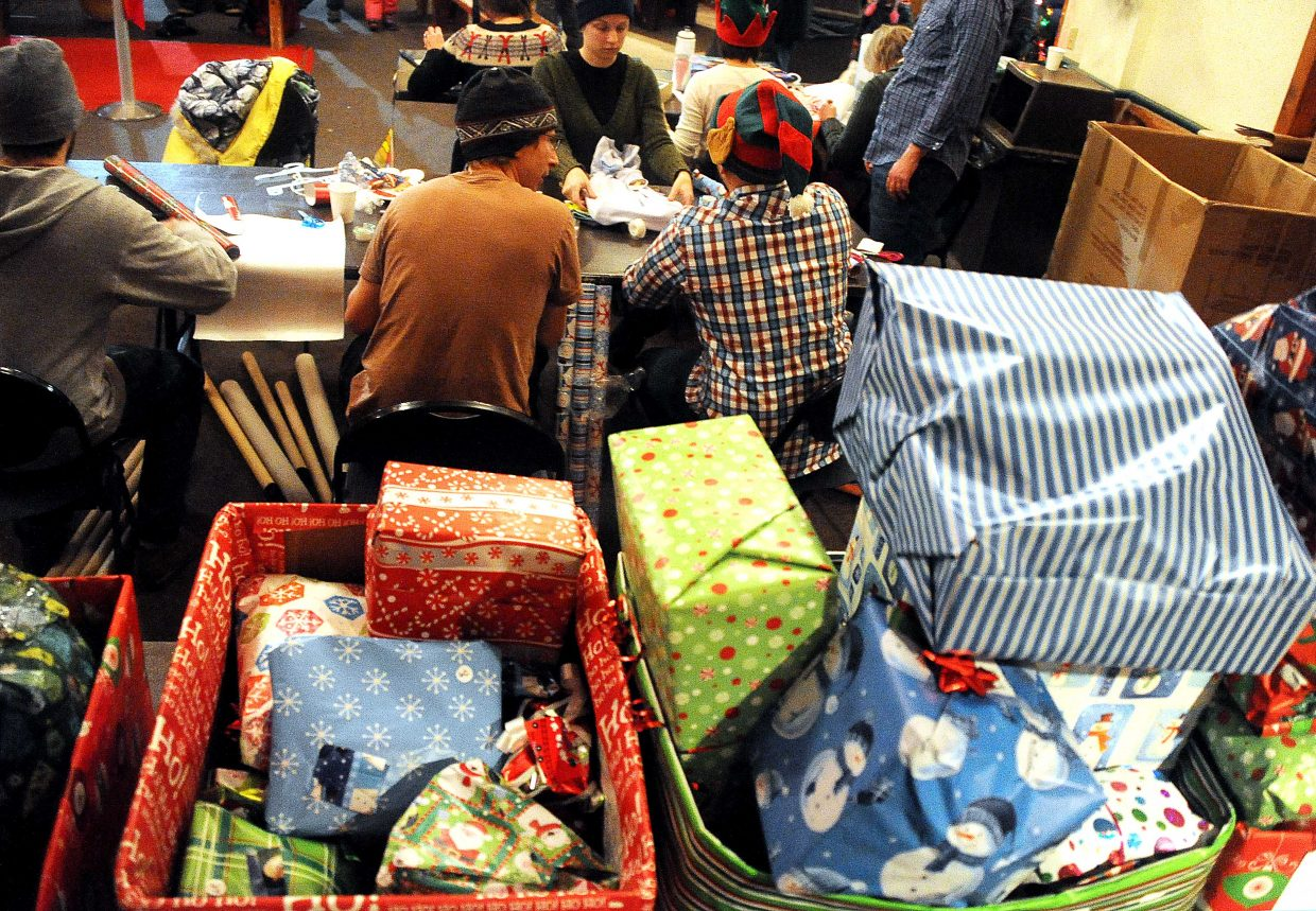 Volunteers wrap presents near a big stack they've already gotten Sunday during the Holiday Wishes party at Howelsen Hill in Steamboat Springs.