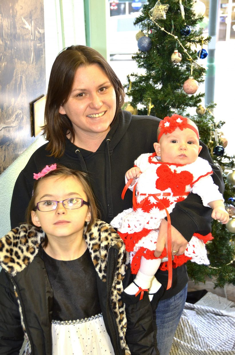 Rebecca Claypoole, center, holds her 3-month-old daughter, Loveaya Claypoole, and stands with her niece Lariah Cramblett, 7, at the Craig Daily Press' annual Letters to Santa event Wednesday.