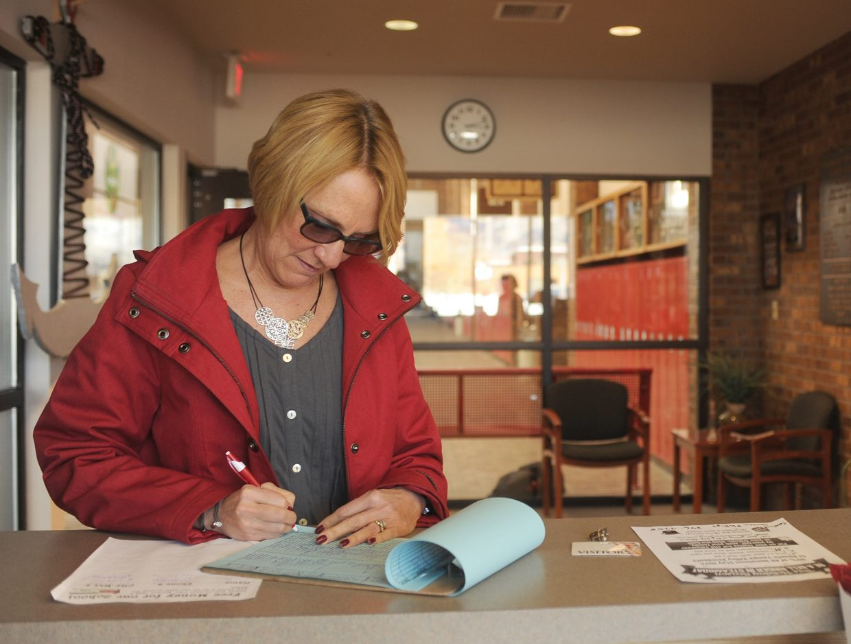 Pam Ruehle signs in at the Steamboat Springs Middle School on Monday afternoon. All visitors are buzzed into the building and are required to check in and the front desk, where they sign in and are issued a visitors pass.