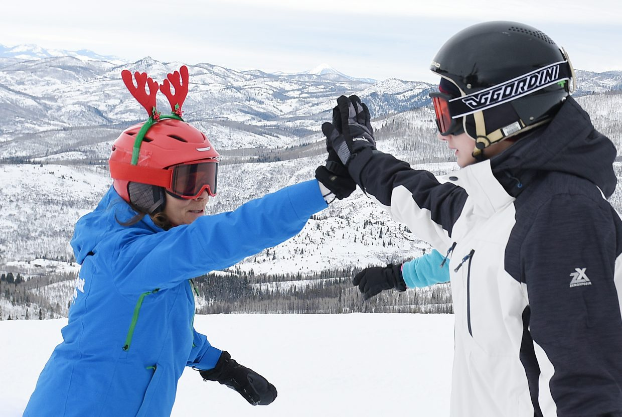Steamboat Ski Area instructor Allison Tate hands out a high five Thursday during a ski camp for children with burn injuries in Steamboat Springs.