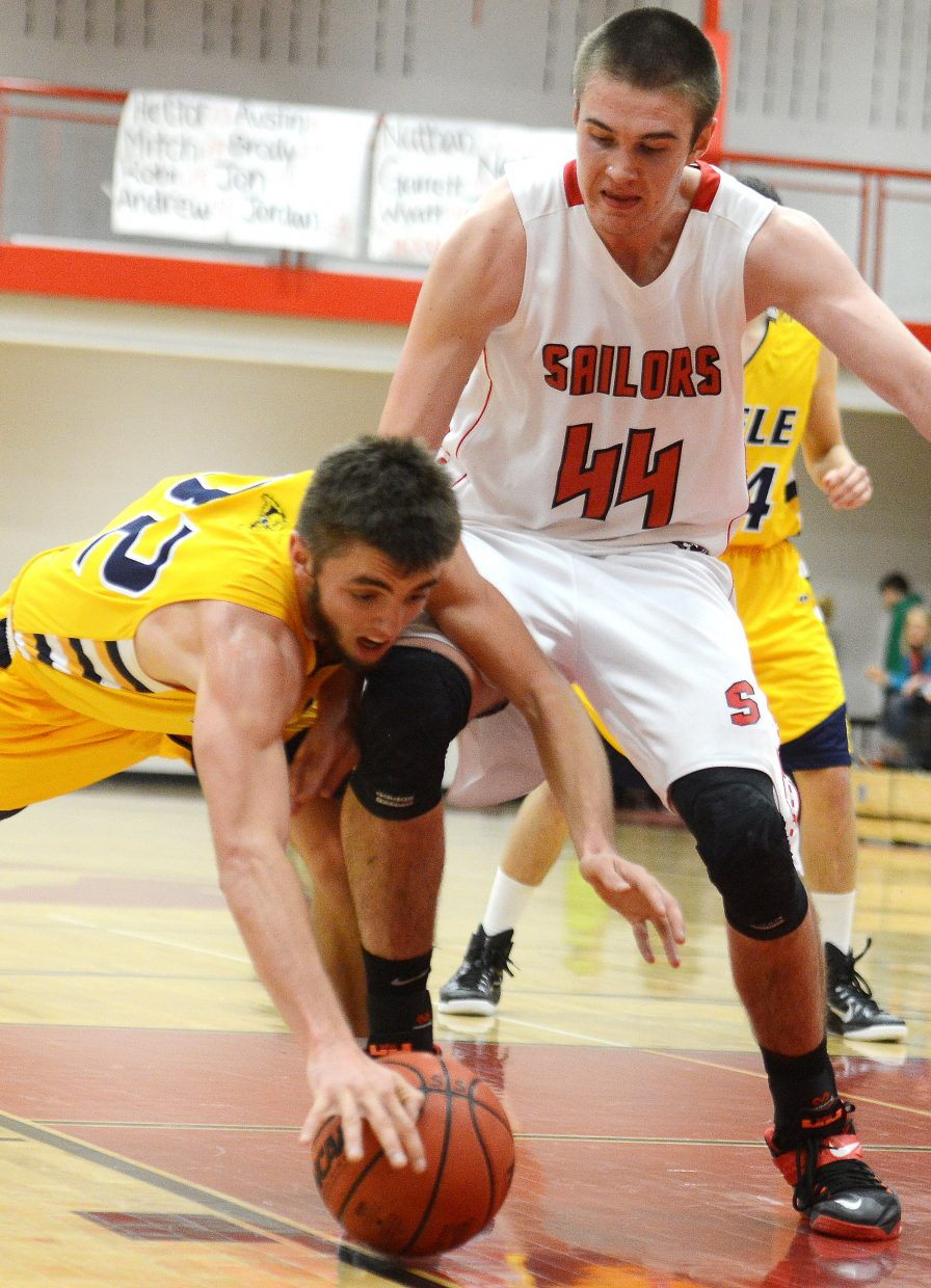 Rifle's Cody Rice dives over Garrett Bye's knee on Wednesday to try to track down a loose ball.