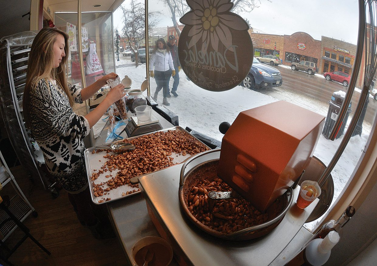 Courtnee Weiss was helping the owners of The Homesteader keep up with the holiday rush Wednesday as she packaged cinnamon vanilla cashews in front of the businesses window looking out on Lincoln Avenue in downtown Steamboat Springs.