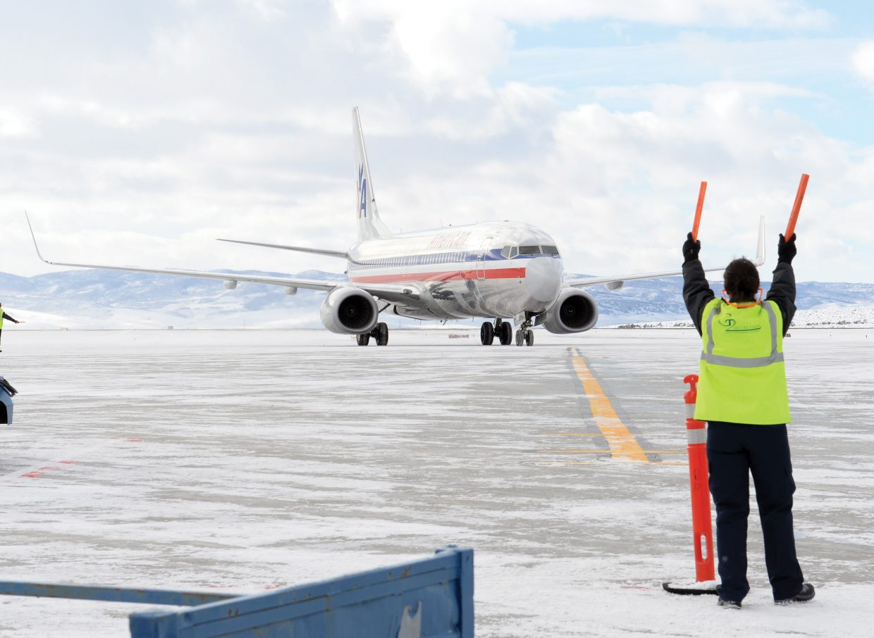 A member of the ground crew guides an American Airlines flight full of visitors from Houston into the Yampa Valley Regional Airport on Thursday afternoon.