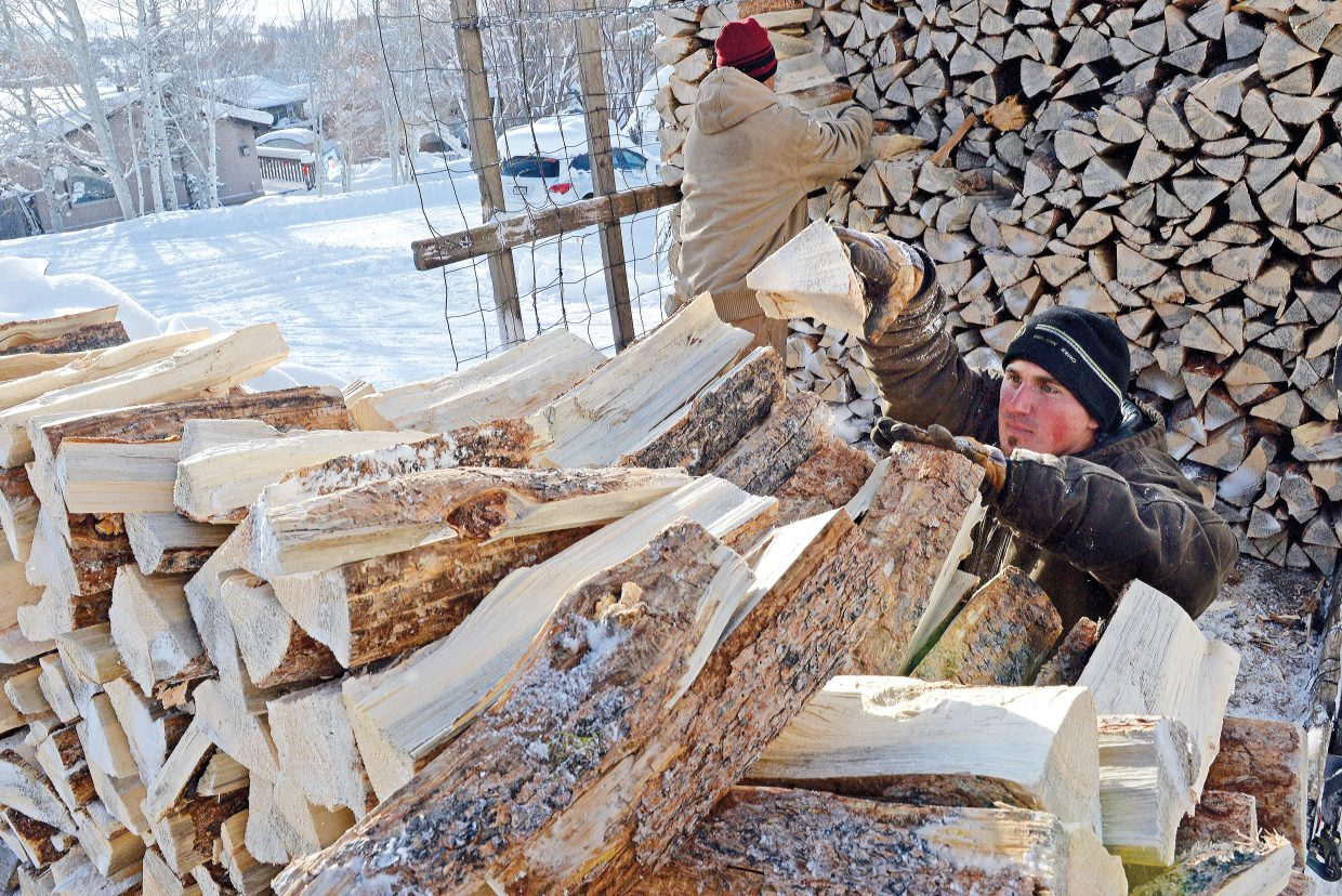 Albert Gonzales and his cousin Pete deliver firewood to a home in Steamboat II Thursday morning. Gonzales said it's a busy time of year for the company, Gonzales Firewood and Tree Services, as they attempt to keep up with customers who use wood to heat their homes.