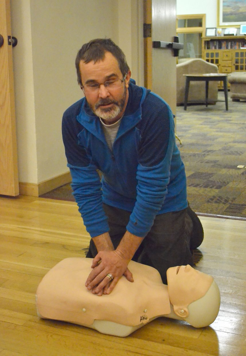 Brian Arel practices CPR on a dummy at the Steamboat Springs Community Center Thursday night.