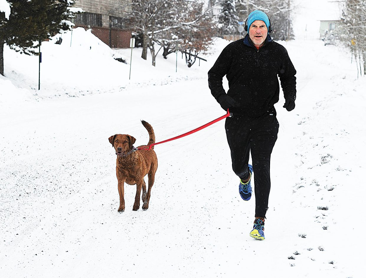 Mike Fallon and his dog Makita run through the snow in downtown Steamboat Springs on Friday morning.