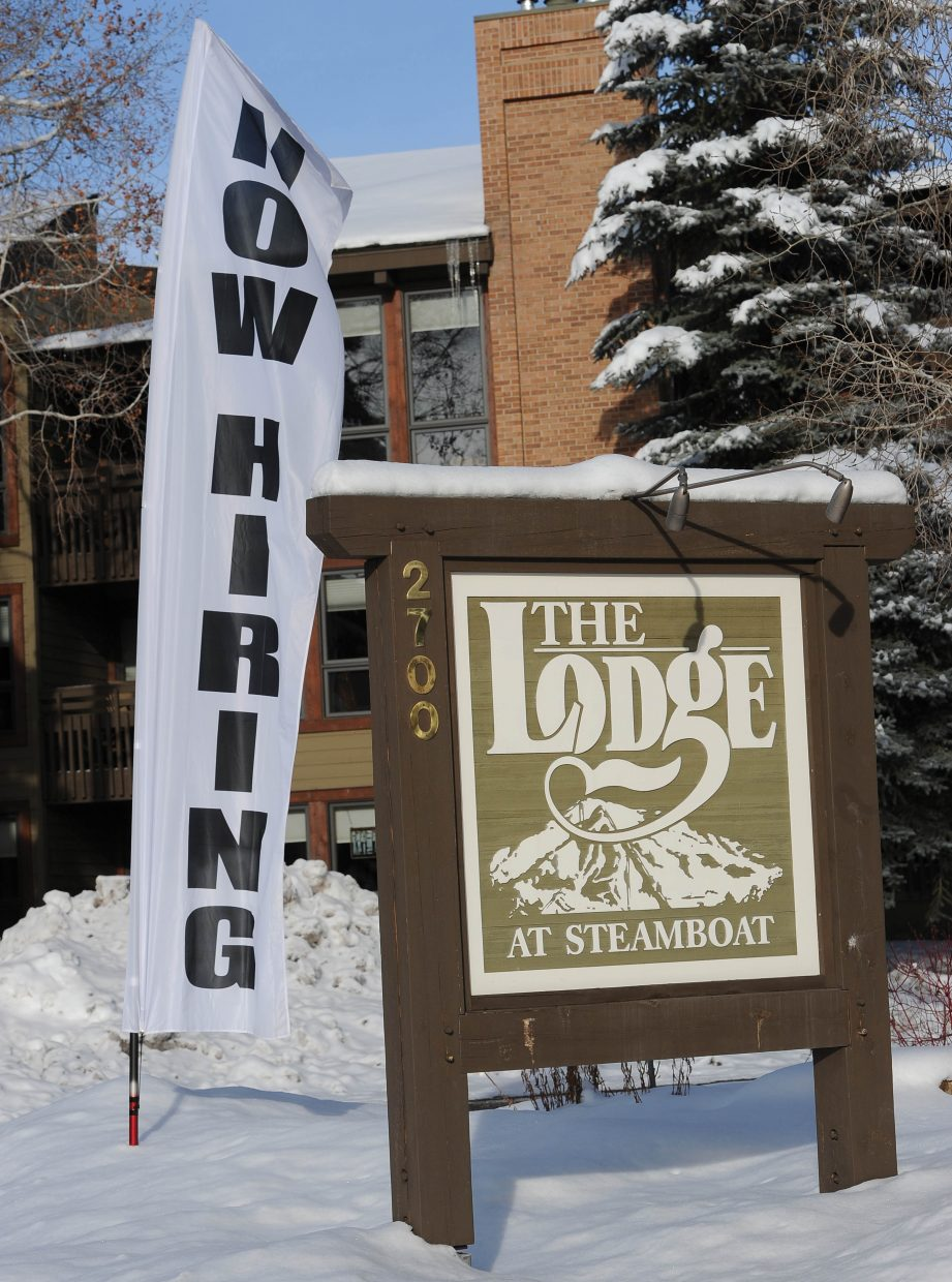 """A """"now hiring"""" banner waves in the wind Friday at The Lodge at Steamboat. Economists predict a swell in job growth in 2015."""