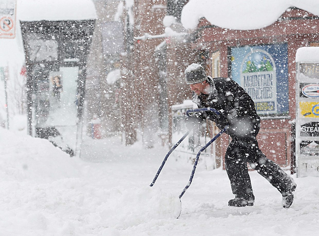 Mathew McLaughlin shovels the walkway in front of Old Town Square Monday morning. A winter storm dropped 9 inches of snow at Steamboat Ski Area overnight and Monday morning, with more snow expected through Wednesday.