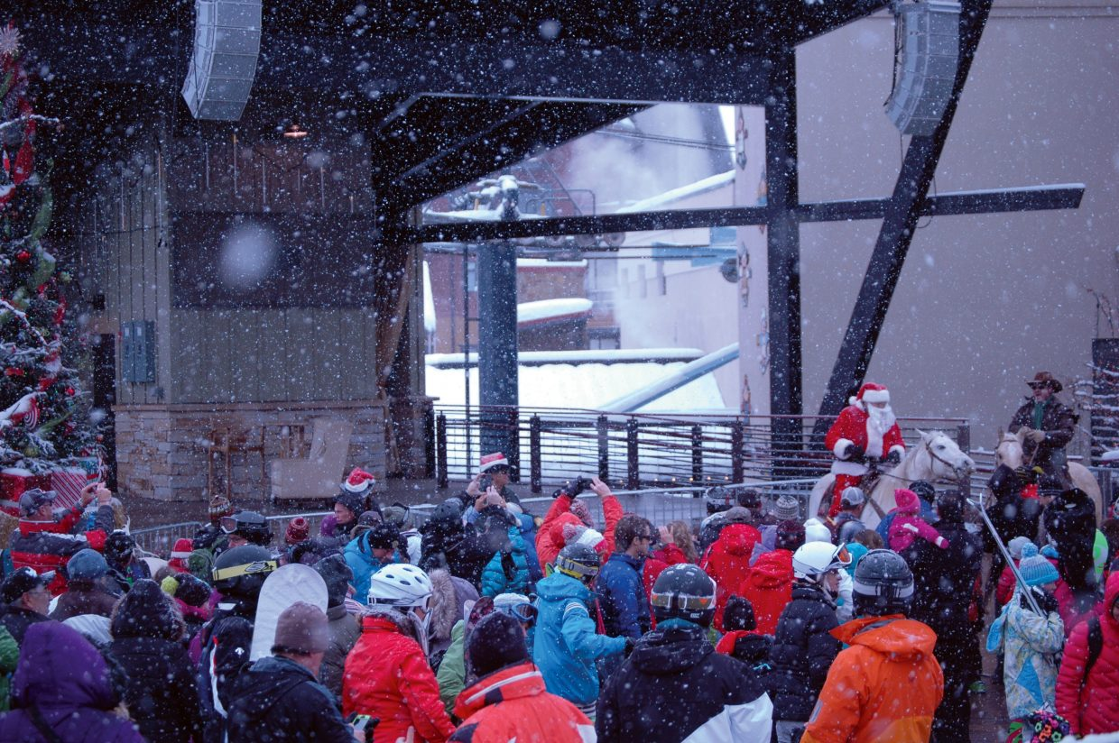 Santa and Bob Dapper greet the crowd at Steamboat Ski Area during the Season's Greetings event Sunday.