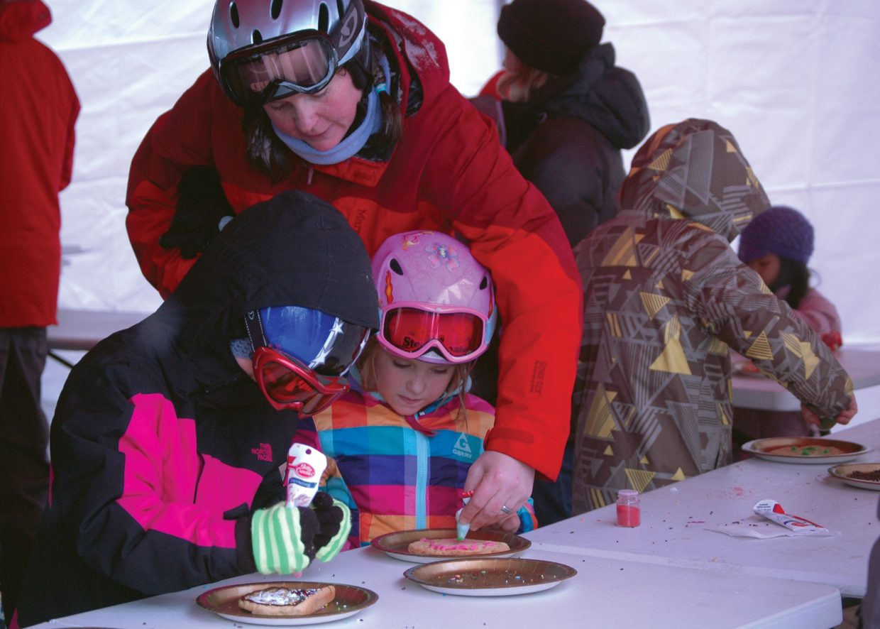 Rebecca Remington helps her daughter Abby with decorating her cookie Sunday during the Season's Greetings event at Steamboat Ski Area. The ski area hosted a couple of reindeer and a visit from Santa along with the cookie decorating for kids.