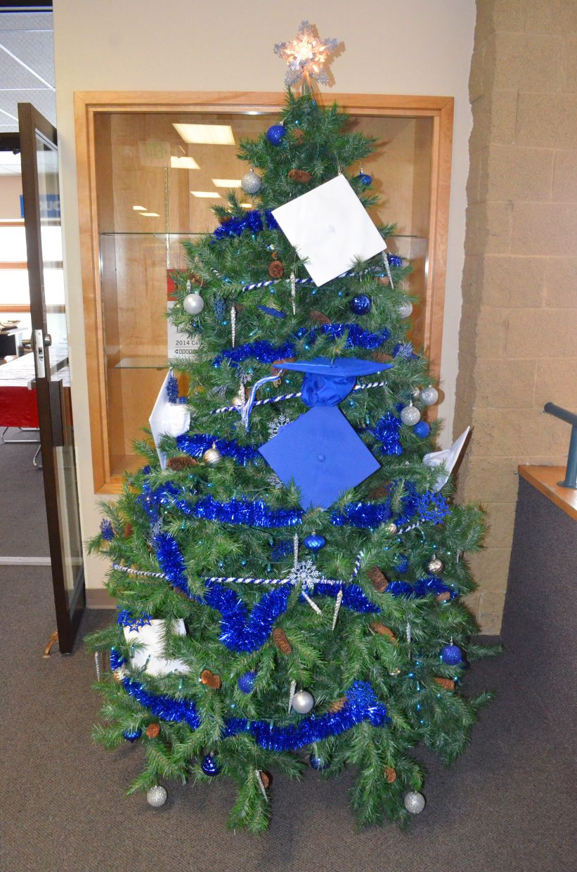 Moffat County High School's second floor Christmas tree is adorned with blue and white decorations, including graduation caps in the school colors.