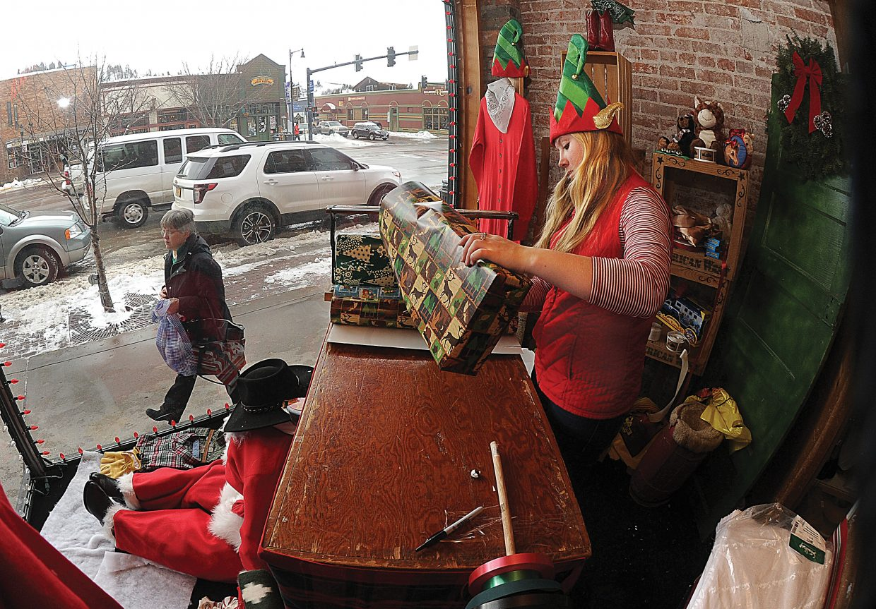 """With one more shopping day until Christmas, """"elf"""" Lauren Graham on Tuesday was spreading the holiday spirit while wrapping gifts in the front window of F.M. Light & Sons on Lincoln Avenue in downtown Steamboat Springs. The downtown area was busy Tuesday as shoppers looked for those last-minute gifts and retail stores offered things like gift wrapping to get customers in the doors."""