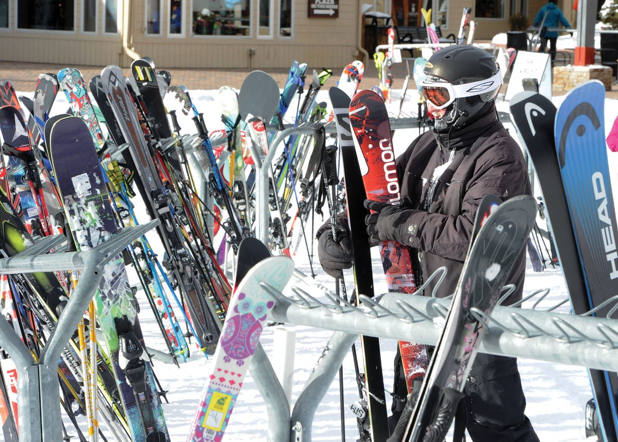 Carl Spangler, of Bailey, places his skis in the packed racks near Slopeside Grill on Tuesday afternoon. Skiers visiting Steamboat Springs this week should have some good conditions as more snow is expected in the next few days.