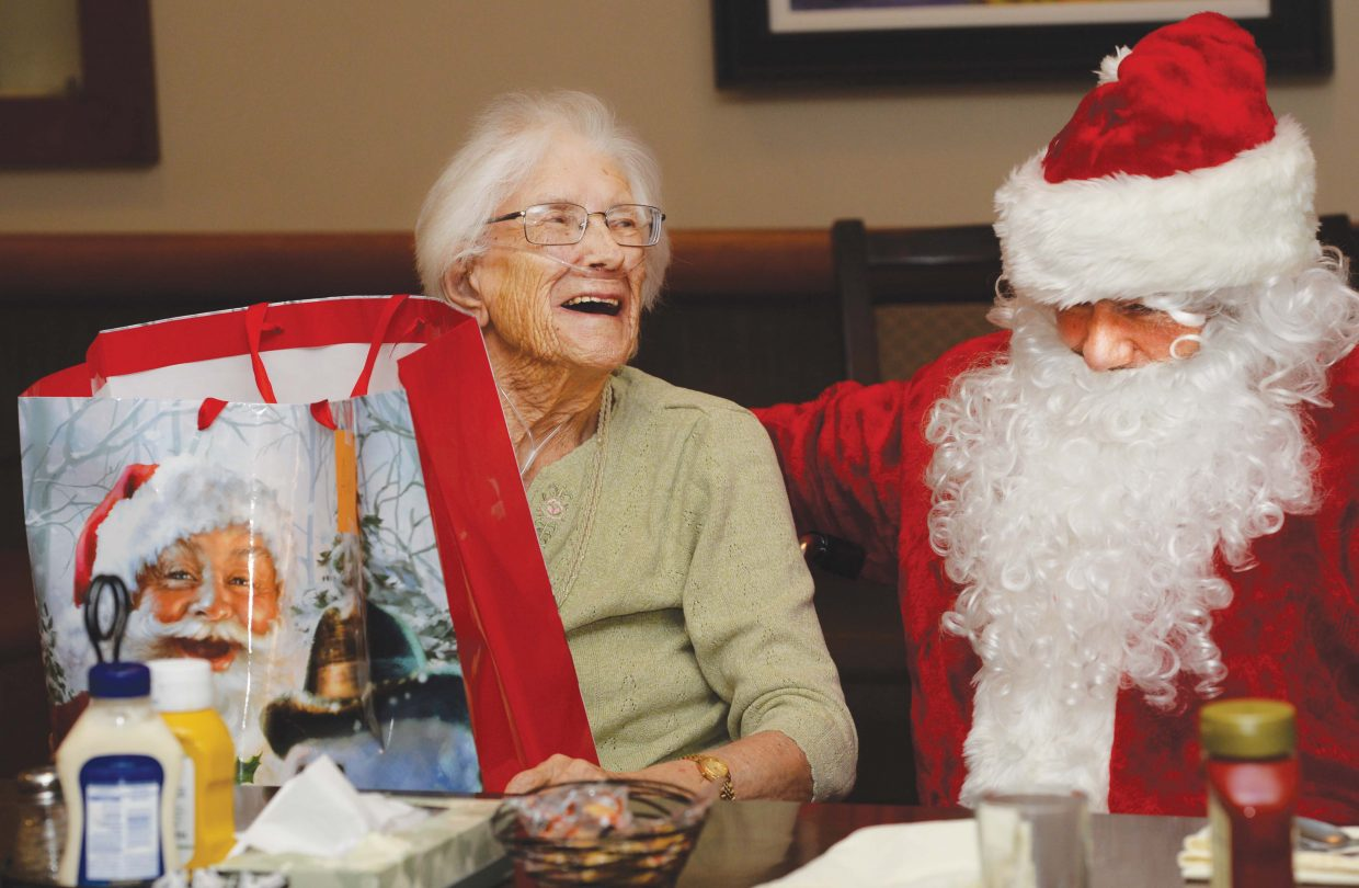 Doak Walker House at Casey's Pond resident Alice Coulter laughs while visiting with Santa Claus during a surprise appearance at the extended care center facility Wednesday afternoon. Santa brought presents collected for the holiday by Routt County Human Services employees and their families. The presents were distributed by Santa and a few helpers at Doak Walker to brighten the holidays for residents.