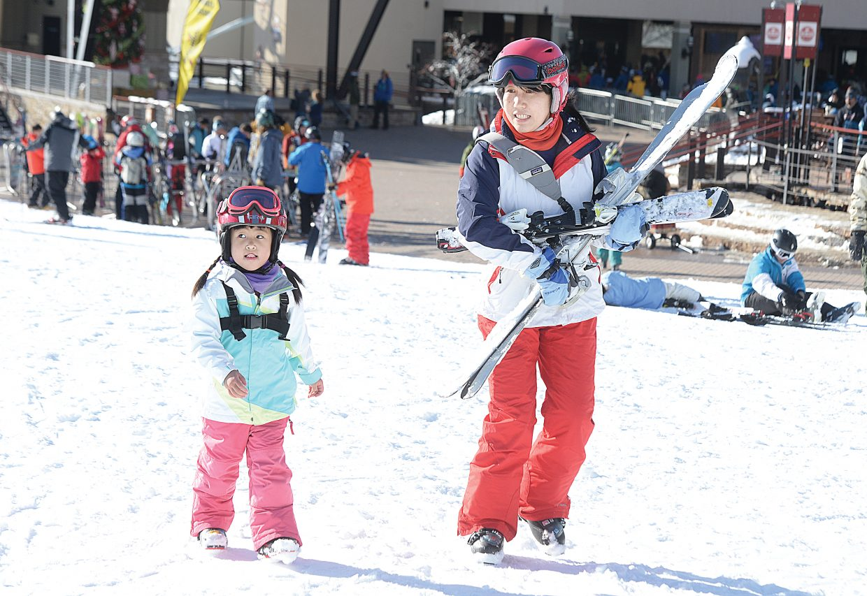 Qian Dng and her daughter Katie Cui head toward the Christy Express lift Friday morning. There are sure to be plenty of skiers flocking to the slopes of Steamboat Ski Area the next few days as the busy holiday season shifts into high gear.
