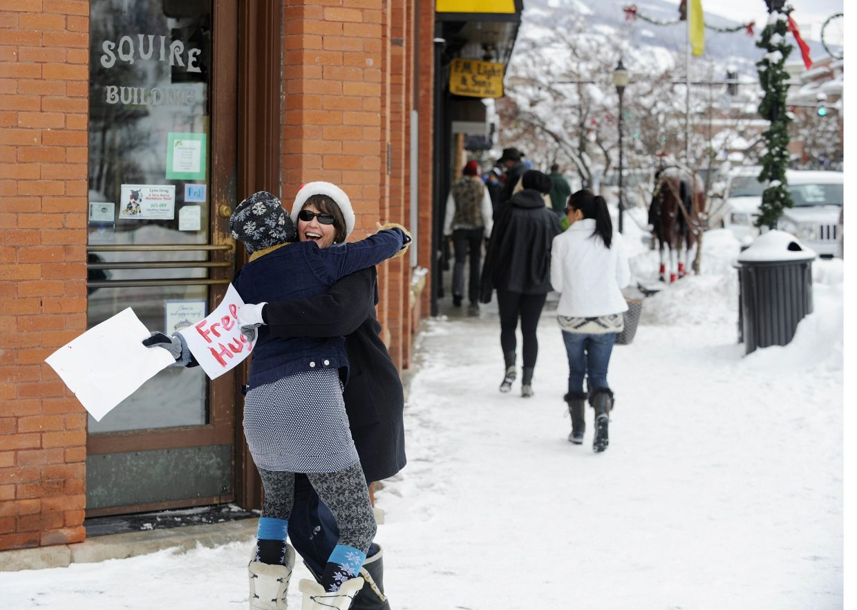 """Beth Musselman spreads holiday cheer Tuesday afternoon by giving away free hugs to passers-by in downtown Steamboat Springs. Musselman and her family were giving hugs with the Good and Petersen families. """"We just wanted to come and spread some love,"""" Petersen said. Musselman's husband, Todd, also was singing Christmas songs."""