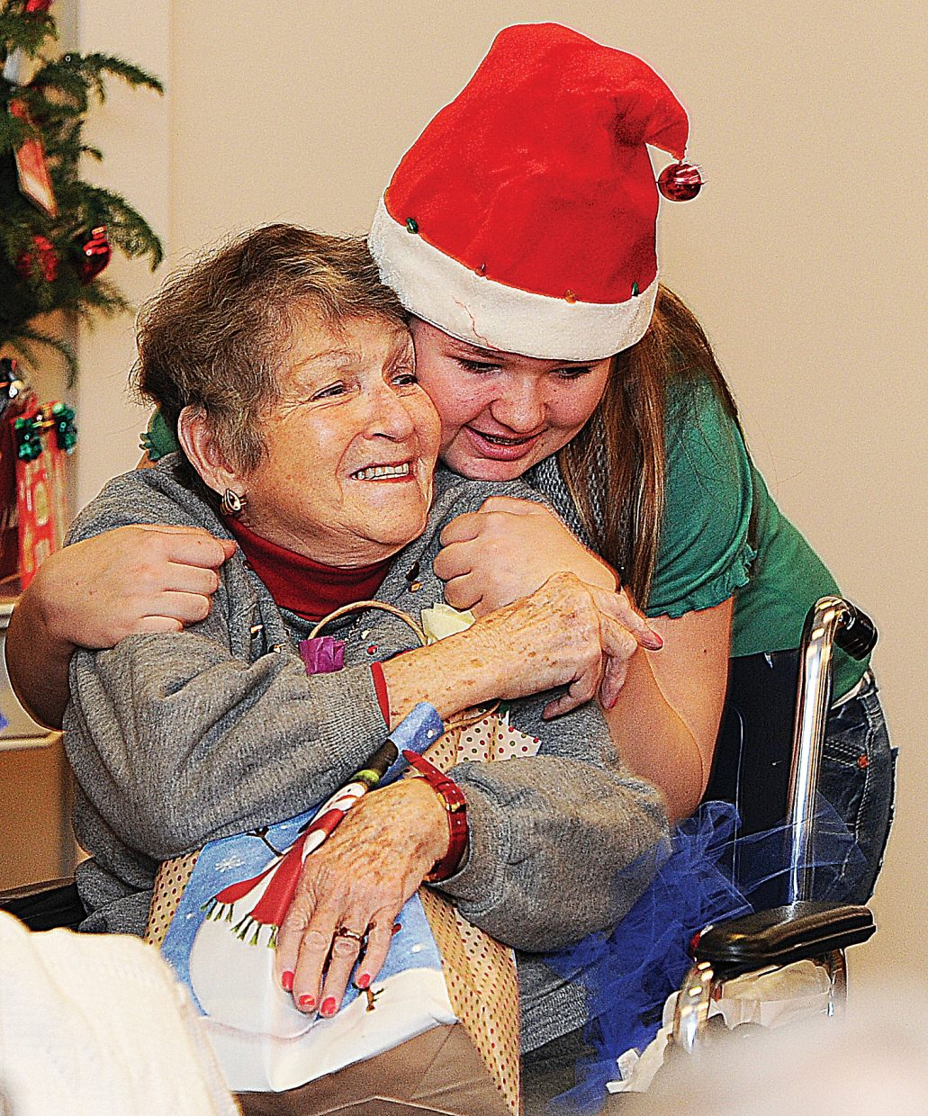 Katelyn Hoffman hugs Bettie Pierce while handing out presents at the Doak Walker House on Wednesday morning. The presents were collected and donated by Routt County employees who adopted the Doak Walker residents. Santa and his helpers spread the holiday cheer on Christmas Eve.
