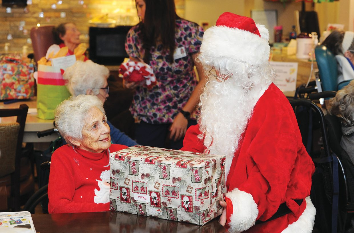 Santa Claus, played by Chance Reynolds, delivers a gift to Veda Wyman at the Doak Walker House on Wednesday morning. The presents were collected and donated by Routt County employees who adopted the Doak Walker residents.