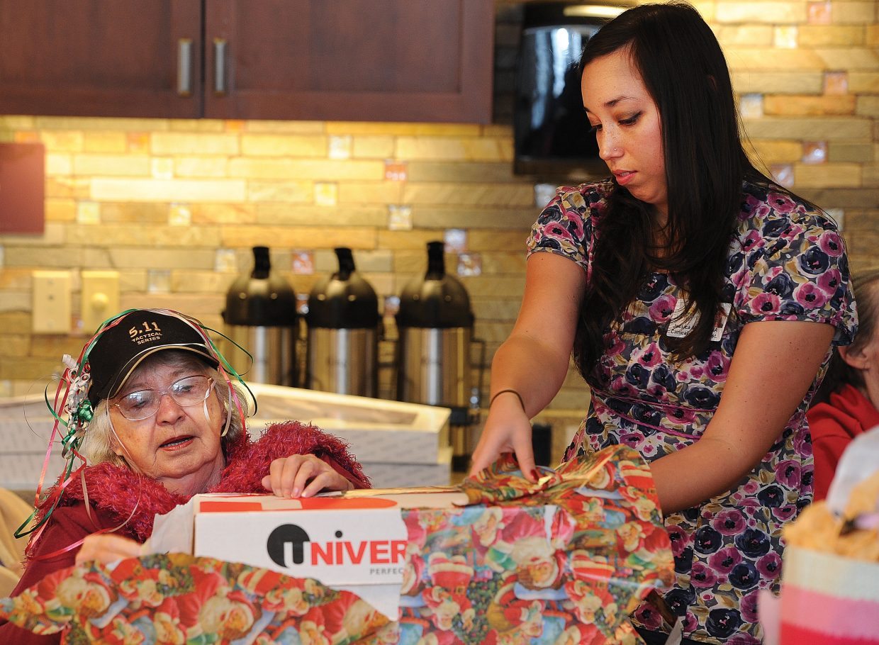 Nurse Jessica Moon helps Lexie Iacovetto unwrap a present Wednesday during a party at the Doak Walker House. The presents were collected and donated by Routt County employees who adopted the Doak Walker residents. Santa and his helpers spread the holiday cheer on Christmas Eve.