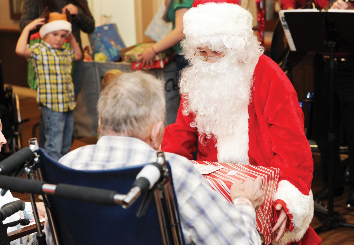 Santa Claus, played by Chance Reynolds, delivers a gifts to residents Wednesday at the Doak Walker House.