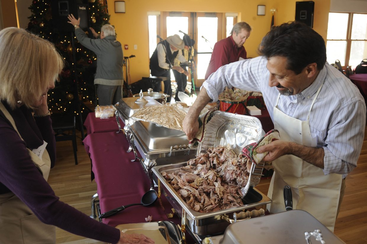 Loui Antonucci gets the turkey ready for the Community Christmas Dinner on Wednesday at the Steamboat Springs Community Center.
