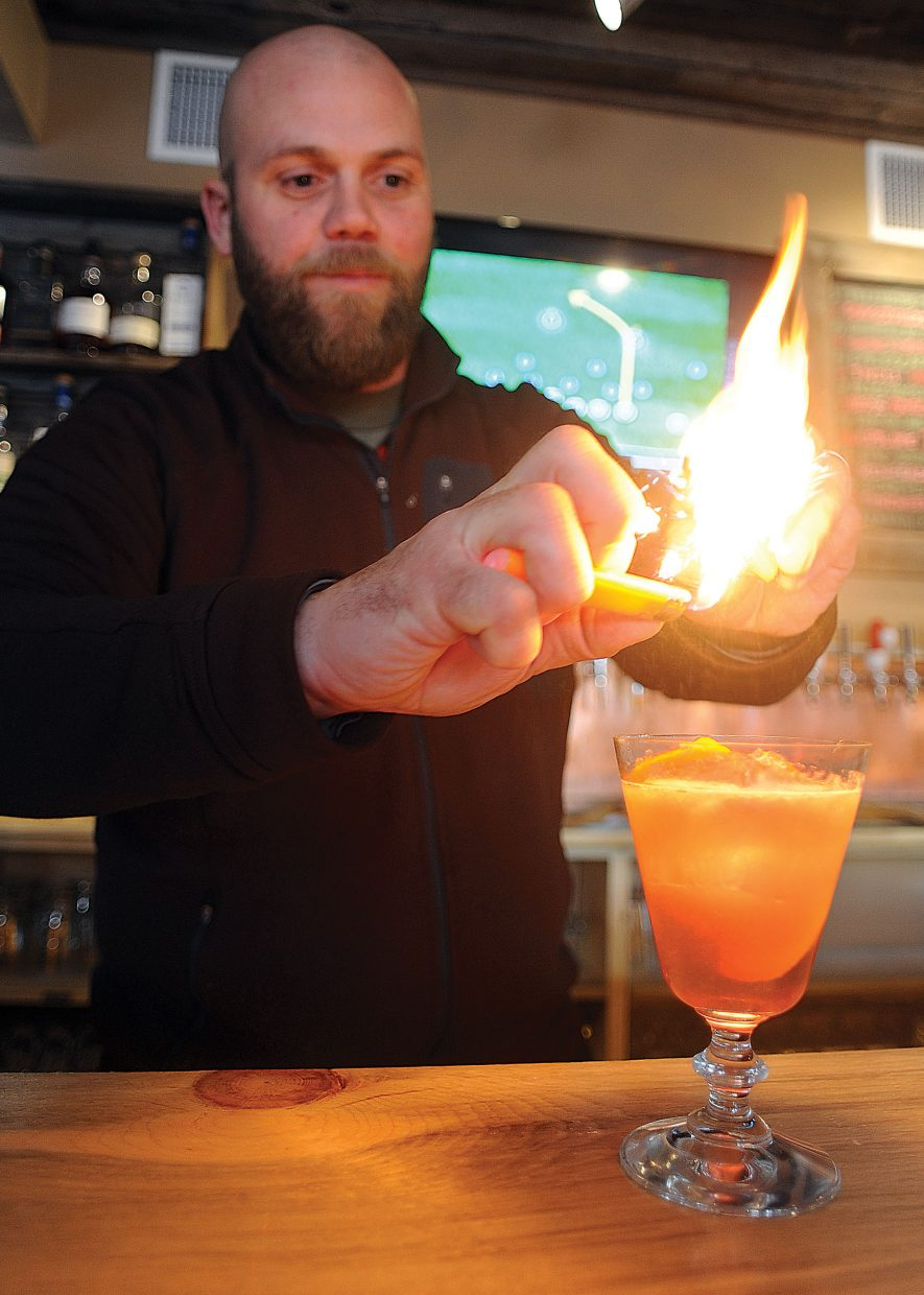Bartender Michael Ruby uses a lighter to ignite the juices from fruit while making a specialty drink at the BARley in downtown Steamboat Springs. The BARley features several Jam Cocktails. This one featured the choke cherry jam from Cider Fixins and the Fireside Bourbon Whiskey, also from Colorado. Ruby uses the lighter to give the drink a smoky taste.