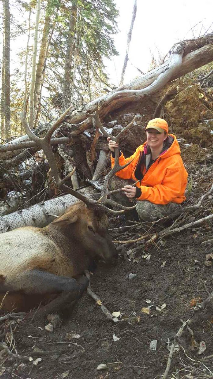 Craig's Kristin Grajeda holds up a six-point bull up by its antlers. She harvested the animal during hunting season near Black Mountain.