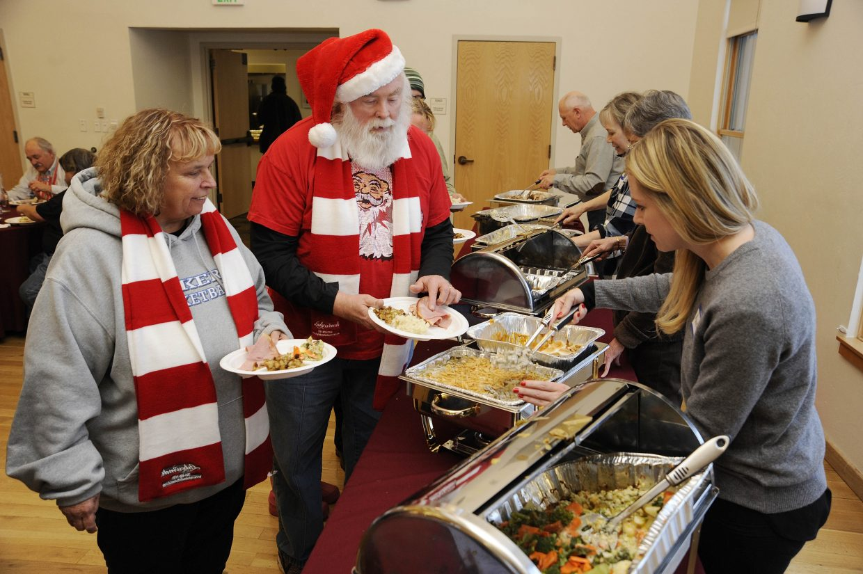 Michigan residents Colleen and Gary Klingler go through the food line at the Community Christmas Dinner, which was hosted by the Steamboat Springs Board of Realtors on Friday at the Steamboat Springs Community Center.