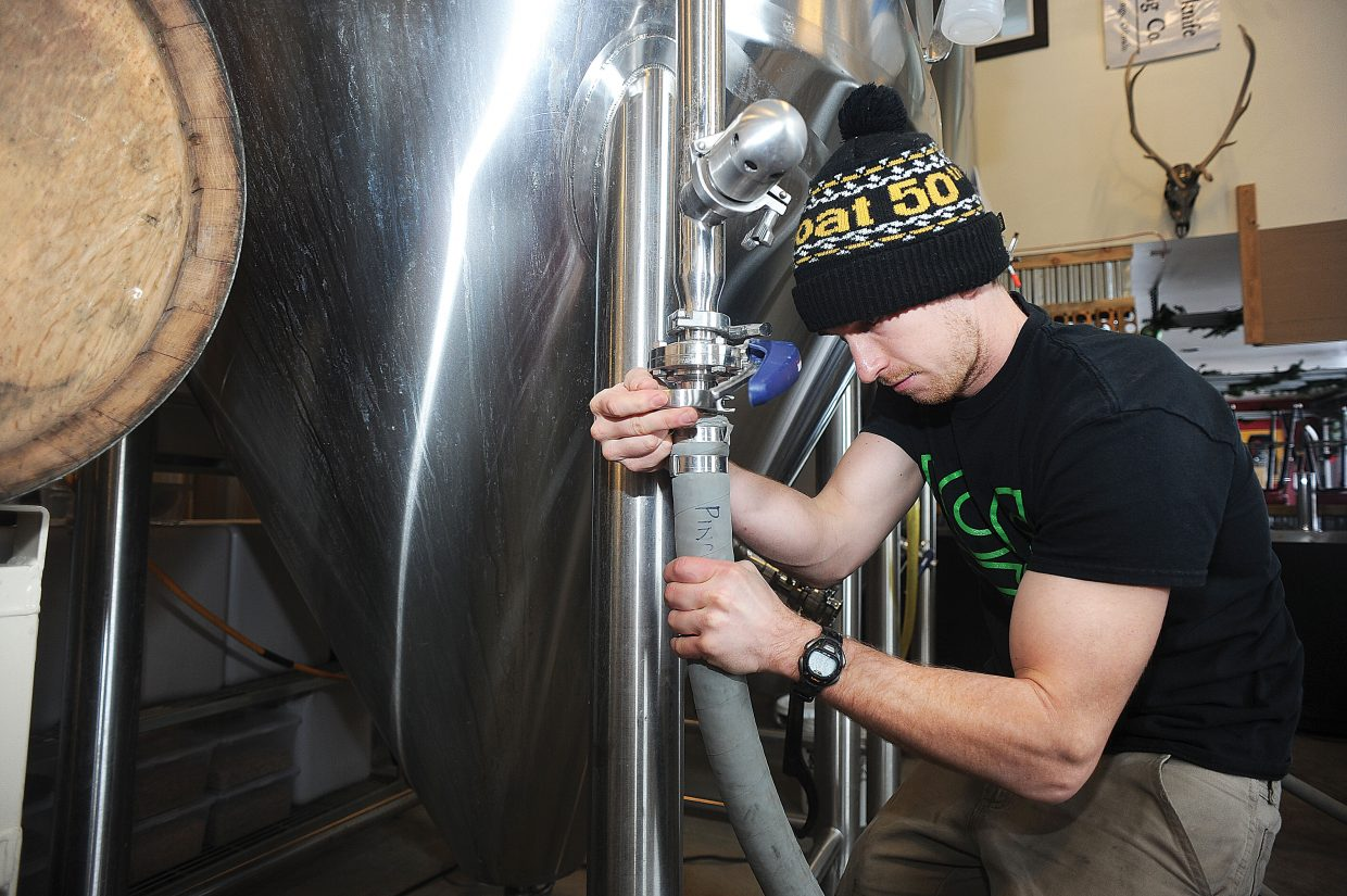 Rob Schwarz hooks up a hose while sanitizing a fermentor at Butcherknife Brewing Co. in Steamboat Springs.