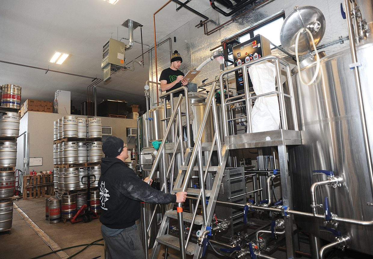 Nate Johansing, who owns Butcherknife Brewing Co. with Mark Fitzgerald, goes over the data with Rob Schwarz while brewing Hefeweizen at Butcherknife Brewery in Steamboat Springs.