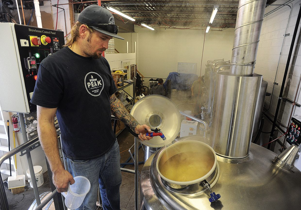 Tyler Patterson, who owns the Storm Peak Brewery with his brothers and father, sprays water into brew kettle while making Funky Touch.